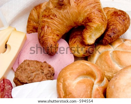Breakfast table with cloth, diversity of bread and sandwich filling, meat and cheese.