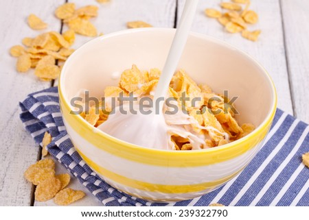 Breakfast table with cornflakes cereal and milk - stock photo