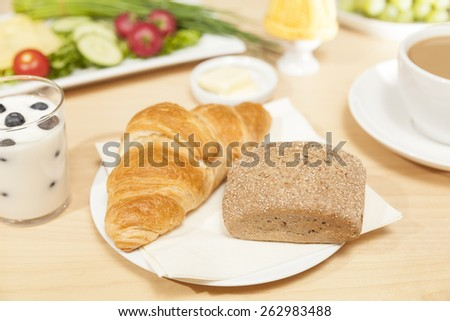 breakfast table with croissant and roll - stock photo