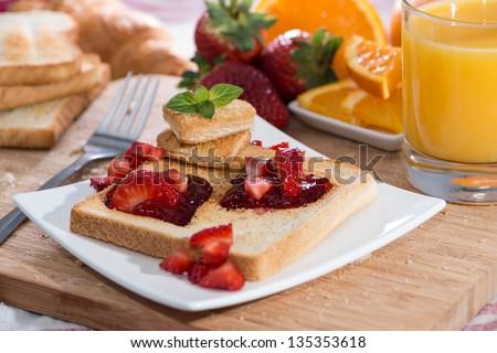 Breakfast Table with toast, strawberry jam and orange juice - stock photo