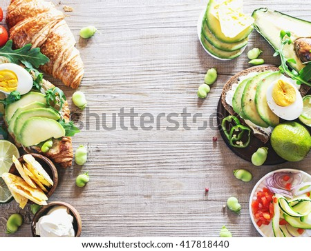 Breakfast table with various ingredients, avocado sandwich, health diet concept. Top view. - stock photo