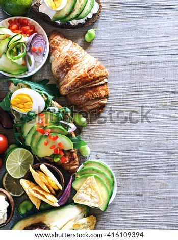 Breakfast table with  various ingredients, avocado sandwich, healthy diet concept. Top view. - stock photo