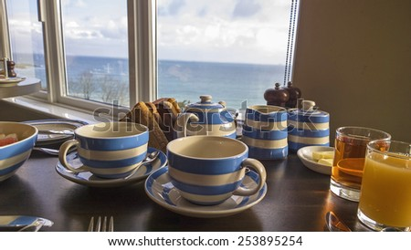 Breakfast tea with a view over the sea in cornwall, tea cups on a breakfast table shot in an artistic composion with the view from the window shown in the background - stock photo