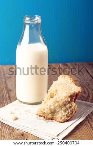 Breakfast time (milk and rye bread on a wooden table). Selective focus - stock photo