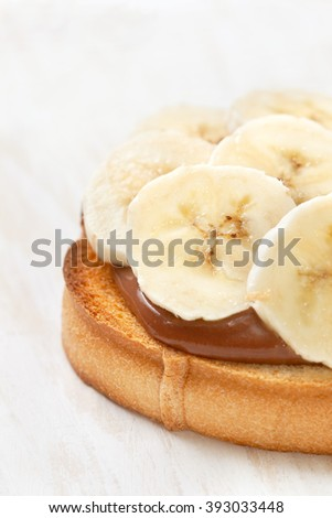 breakfast toast with banana and chocolate cream on a white wooden background - stock photo