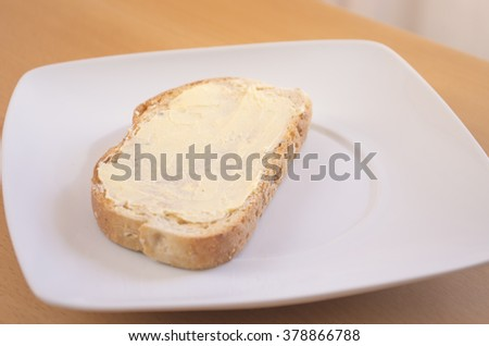 Breakfast. Toast with butter on a white plate with natural light on a table.  - stock photo