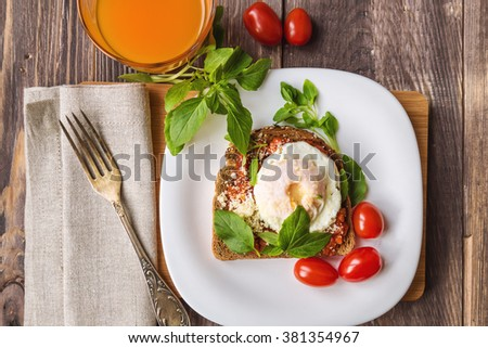 Breakfast toast with poached egg, tomato sauce, basil and parmesan cheese on rustic wooden background
