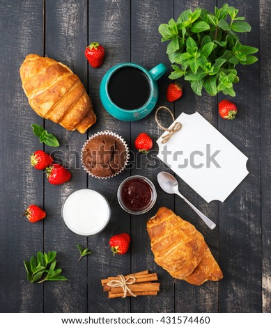 Breakfast Top View. Coffee, Berries, Milk and Sweet Cakes on Black Wooden Background. Rustic Cover Menu. - stock photo