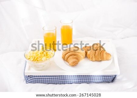 Breakfast tray laying on white bed in home. - stock photo
