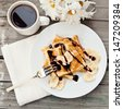 Breakfast : waffles with bananas, chocolate syrup and coffee. Selective focus - stock photo