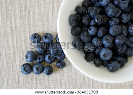 Breakfast: white bowl on linen surface filled with fresh, ripe blueberries.