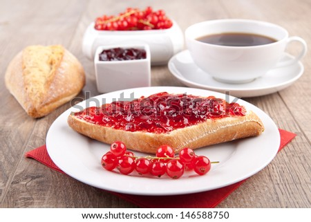Breakfast with a bread roll, jam and coffee - stock photo