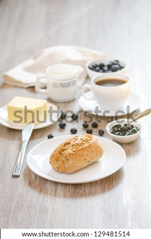 Breakfast with bagel, milk, butter, huckleberry jam and coffee
