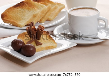 Breakfast with black coffee, toasts, and chocolate
