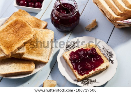 Breakfast with bread toast with cherry jam and a cup of cocoa - stock photo