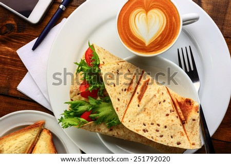Breakfast with cappuccino and sandwich - stock photo