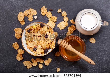 breakfast with cereal flakes, milk and honey on dark background, top view.