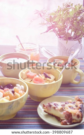 breakfast with cereal mush, fruits, pie and tea for two. On the colorful tablecloth.