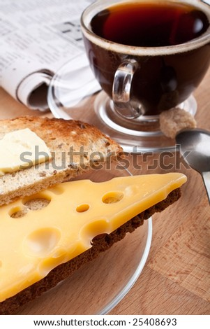 breakfast with coffee, cheese and butter on toast and a newspaper - stock photo