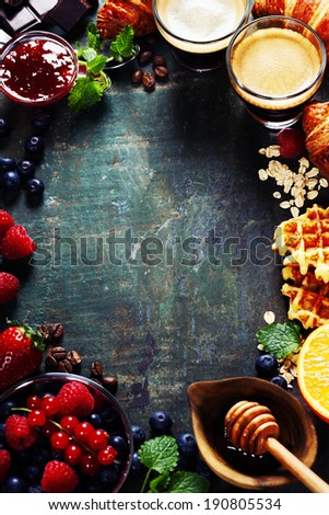 Breakfast with coffee, croissants, honey, chocolate, oats, waffles and berries - stock photo
