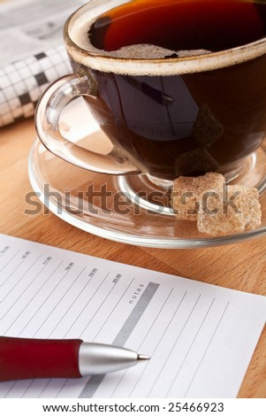 breakfast with coffee, newspaper and a notepad - stock photo