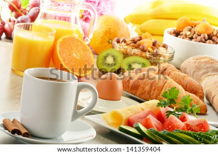 Breakfast with coffee, orange juice, croissant, egg, vegetables and fruits - stock photo