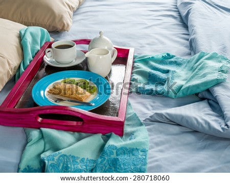 Breakfast with colorful tray on the bed - stock photo