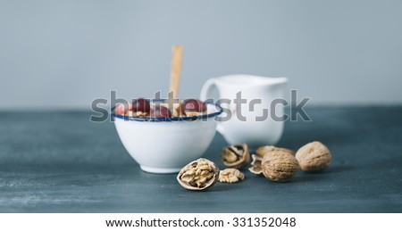 breakfast with cornflakes and milk on dark wooden table - stock photo