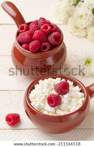 Breakfast with cottage cheese and raspberries in ceramic utensils - stock photo