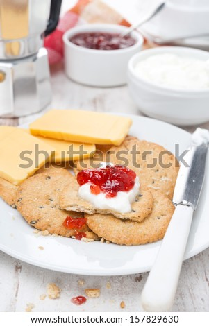 Breakfast with crackers, cheese, cream and berry jam, close-up, vertical