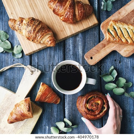 Breakfast with croissants, leaves, cutting board and black coffee composition with girl hand on wooden retro background. Flat lay, top view - stock photo