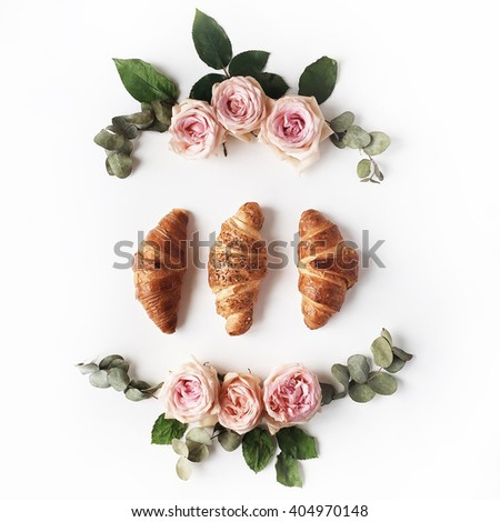 Breakfast with croissants, pink rose flower, petals composition. Flat lay, top view - stock photo