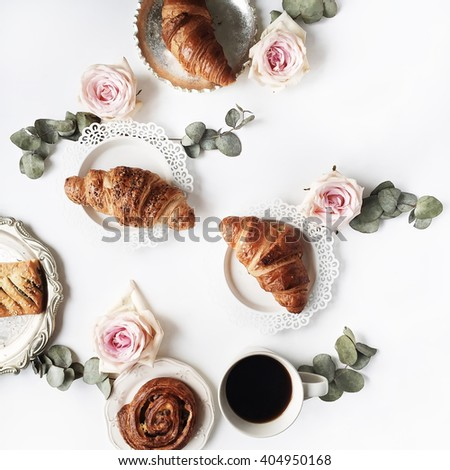 Breakfast with croissants, pink rose flower, petals, vintage plates and black coffee composition. Flat lay, top view - stock photo