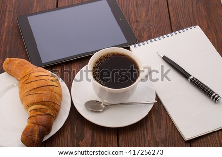 breakfast with cup of black coffee, croissants, the tablet and notebook with pen isolated on white background