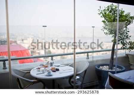 breakfast with cup of black coffee, musli and yoghurt on balcony - stock photo