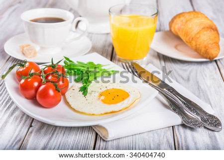 Breakfast with cup of coffee, egg, croissant and orange juice on wooden table - stock photo