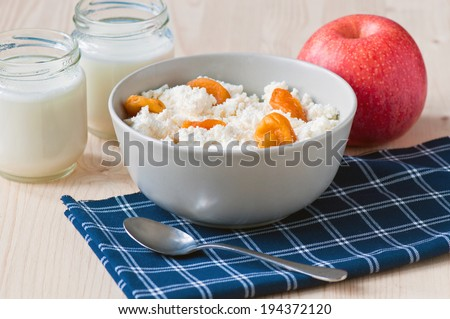 Breakfast with curds, yoghurt, apple and dried fruits - stock photo
