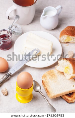 Breakfast with eggs and toasts served with jam and butter over white textile. See series.