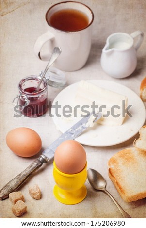 Breakfast with eggs and toasts served with jam and butter over white textile with vintage texture. See series.