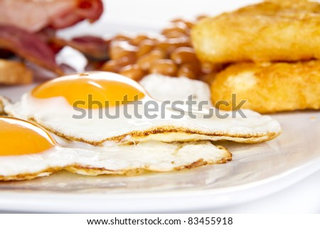 Breakfast with eggs bacon beans and hash browns - stock photo