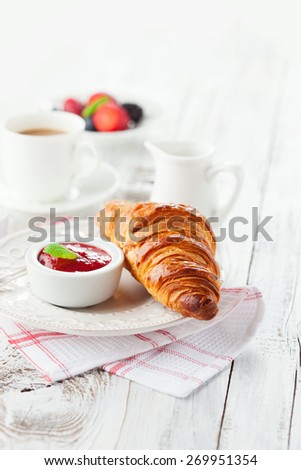 Breakfast with fresh croissants, cup of coffee and strawberry jam on a white wooden background, selective focus - stock photo