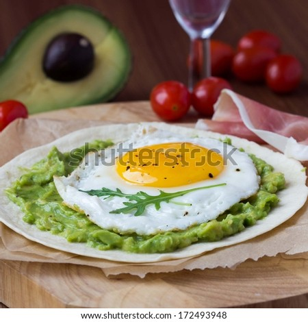 Breakfast with fried egg and sauce of avocado on grilled flour tortilla, Mexican dish huevos rancheros - stock photo