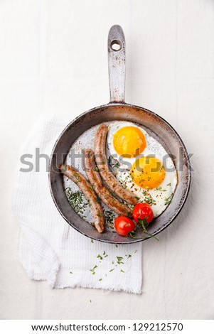 Breakfast with Fried eggs and sausage on pan - stock photo