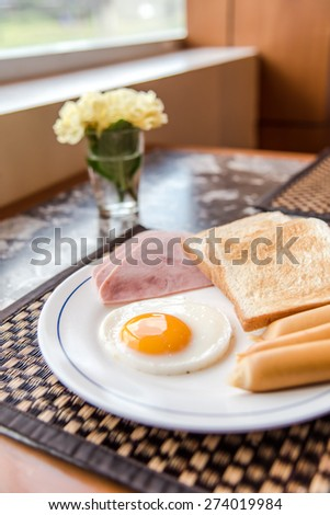 Breakfast with fried eggs, bacon, sausages, toasts - stock photo