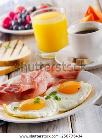 Breakfast with  fried eggs, bacon,toasts,orange  juice and coffee.Selective focus - stock photo