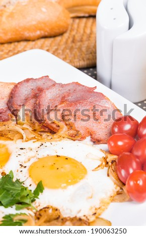 Breakfast with fried eggs beacon onion and fresh tomatoes - stock photo