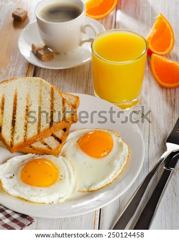 breakfast with fried eggs, toasts, juice and coffee/ Selective focus - stock photo
