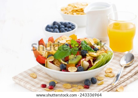 breakfast with fruit and berry salad, juice and cereal, close-up, horizontal - stock photo