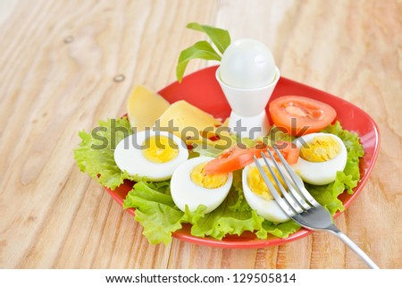 Breakfast with hard boiled eggs, sliced in halves, salad, tomatoes, cheese and bread on the red plate and wooden background - stock photo