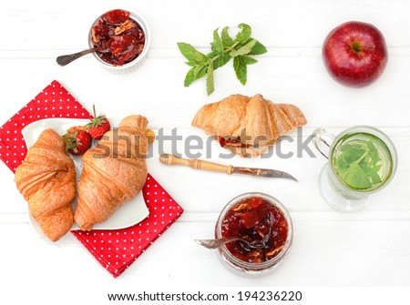 Breakfast with herbal tea, croissants and jam on the white wooden table, top view - stock photo
